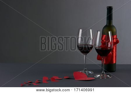 Wine bottle and two wineglasses with red hearts on a gray background. Love card concept with copy space Valentine's day theme