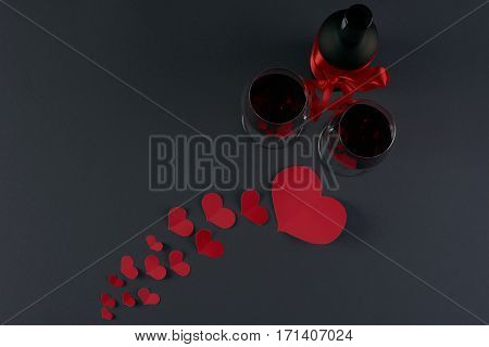 Wine bottle and two wineglasses with red hearts on a dark background. Love card concept with copy space Valentine's day theme. Shot from above