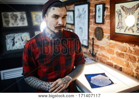 Man with beard, piercing and tattoes working in tattoo salon