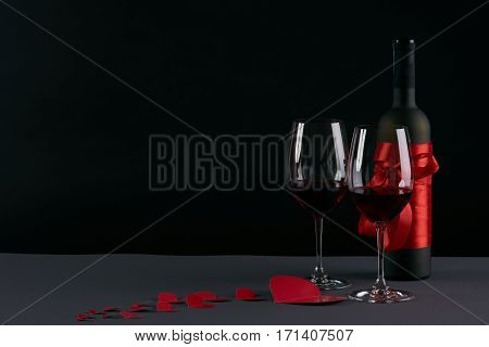Wine bottle and two wineglasses with red hearts on a dark background. Love card concept with copy space Valentine's day theme