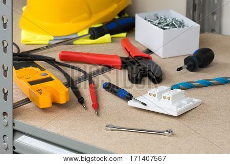 Electrician's Gear And Equipment On Cork-covered Shelving