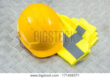 Hard Hat And Folded Safety Vest On Steel Checker Plate