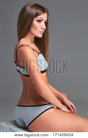 Beautiful girl in sports underwear isolated on gray background. Underwear gray color. The model sits on a chair. Close-up