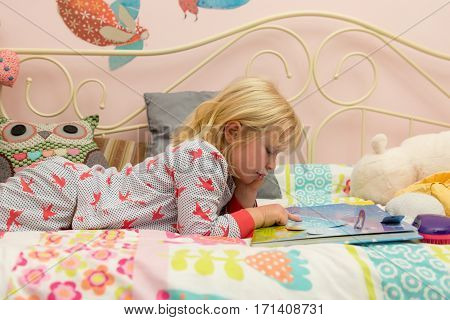 Young Girl In Pj's Reading A Storybook In Bed