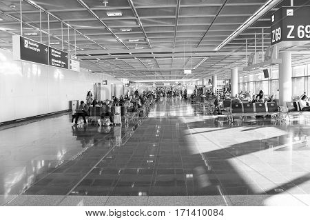 People With Luggage Sitting In Waiting Hall Of Airport