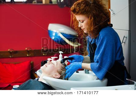 young woman in her hair studio wash hair to female customer small business concept