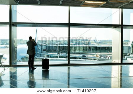 man businessman guy or tourist passenger with suitcase and luggage waiting for flight in airport hall at big window glass holds cell phone