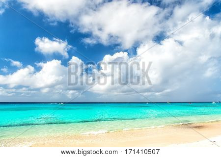 Beautiful marine view on sea coast line with clean wavy surf water on sandy beach with boats and yahts on horizon and cloudy blue sky sunny outdoor at summer vacation