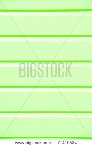 wooden clapboard background of textured siding painted in green color with horizontal lines and nobody as empty or blank backdrop