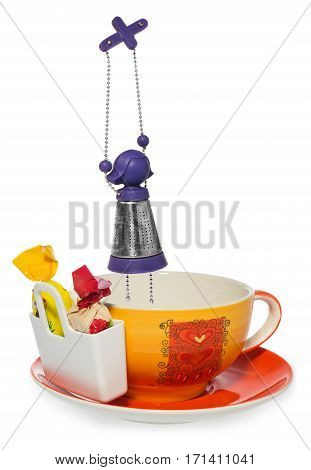 Empty coffee tea cup with purple silver infuser in the shape of a girl on a chain and storage on candy with two sweets . Cup and saucer decorated with hearts in color yellow orange red. Container for sweetmeats in white. Candy in yellow cream red. Dish on