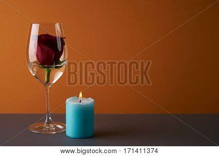 Wineglass with rosebud inside candle and heart on orange background. Love card concept with copy space. Valentine's day theme