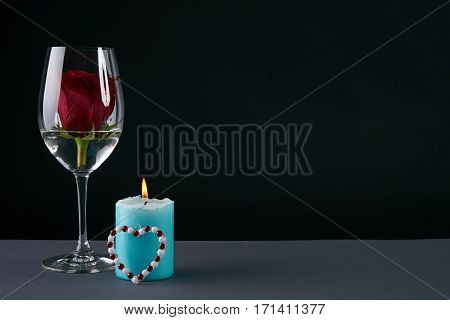 Wineglass with rosebud inside candle and heart on dark background. Love card concept with copy space. Valentine's day theme