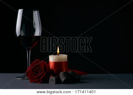 Wineglass with rose candle and chocolate candies on dark background. Love card concept with copy space. Valentine's day theme