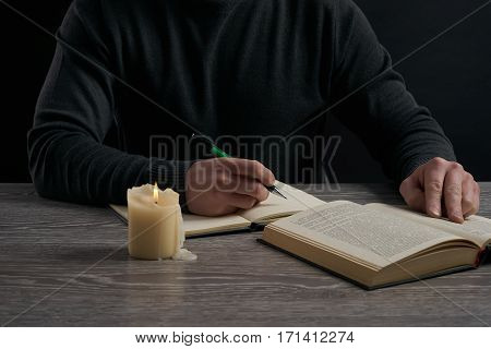 Man in dark sweater studying at wooden table