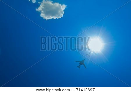 two bombers fly up through the sun on a blue sky background