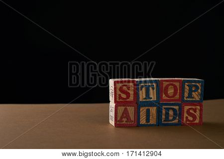 Stop AIDS on Cubes with letters on a table against black background. Copy space