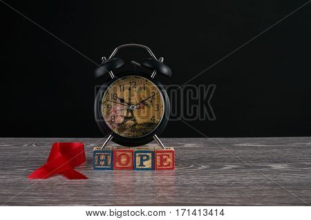 Alarm clock red awareness ribbon and hope word on cubes with letters. Symbol of solidarity with people living with HIV AIDS. Healthcare and medicine concept