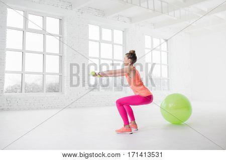 Young woman in colorful sportswear squatting with dumbbells in the white gym with fitness ball on the floor