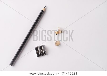 Pencil with sharpening shavings and pencil sharpener on white background
