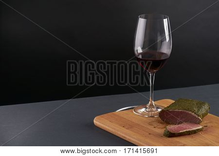 Smoked meat.Spicy bacon and glass of red wine on wooden cutting board.Black background.Copy spase.