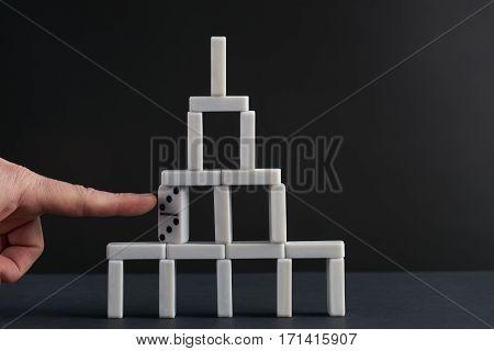 Hand breaking white dominoes tower. Black background