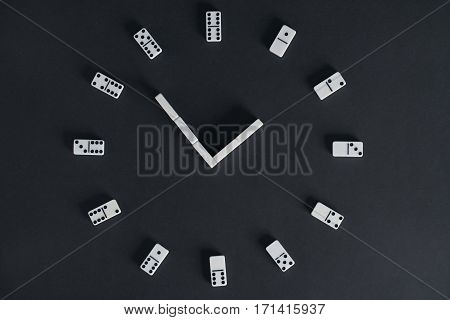 Clock made of domino play chips on dark background. Top view