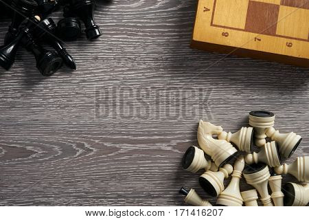 Chess pieces and chessboard on wooden table top view. Copy space