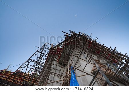 Scaffolding For Buddhism Church Construction With Moon At Evening