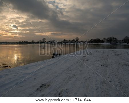 Snow covered road leading to ferry crossing across Vistula river