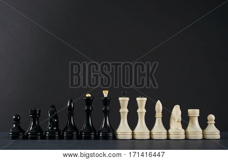Set of black and white chess in classic design on dark background