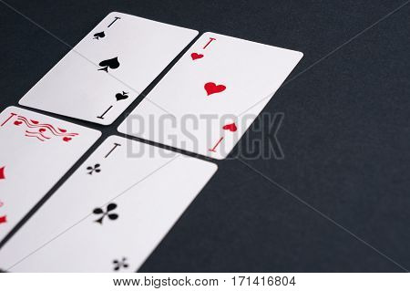 High Angle View of Four pocker Cards Spread Out on Dark Background Showing Aces from Each Suit - Hearts Clubs Spades and Diamonds