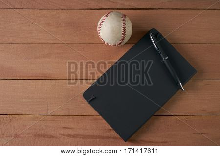 Notebook with pen and baseball ball on an wood table top view
