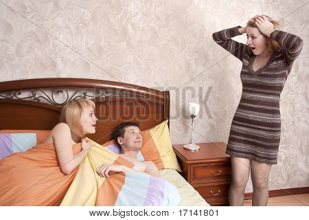 Couple in bed while an angry woman