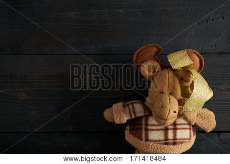Soft toy moose on wooden texture background. Copy space