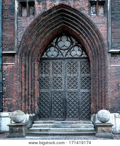 Ancient metal door with portal of gothic church
