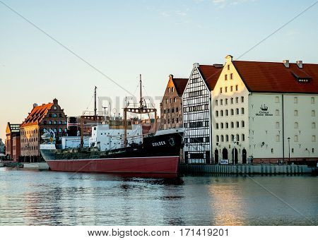 Poland Gdansk - Jule 18 2014: View of the ship-museum freighter Soldek near historic buildings of the island Olowianka. Soldek was the first ship built in Poland after World War II in 1948.
