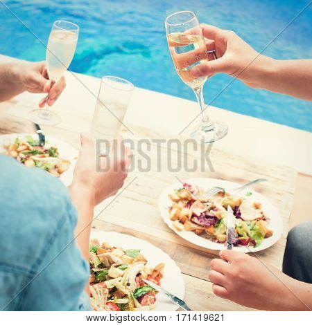 Friends toasting at party by swimming pool. Closeup of hands and plates