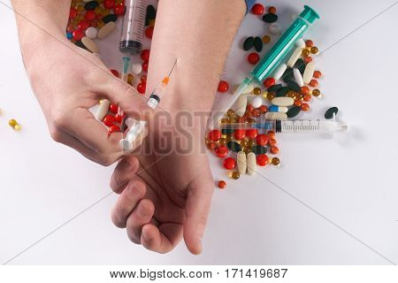 Male hands with medical syringe with drug and different colored medicine and types of pills . Doing inject in vein. On white background.