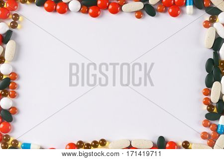 Different colored medicine and types of pills on white background. Medical health or drugs addiction concept with copy space