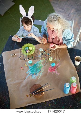 Boy and his grandma painting traditional Easter eggs