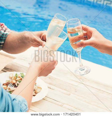Closeup of friends toasting champagne having a dinner by a poolside
