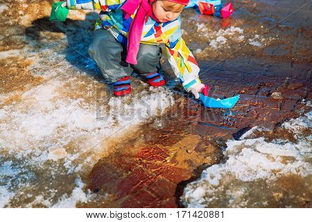 little girl plaing with paper boats in spring puddle, kids seasonal activities