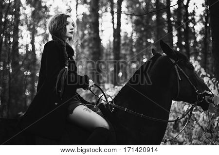 Black and white art photography monochrome brave girl in a black coat and with long hair gathered in a braid a woman riding a horse in autumn forest beautiful strong stallion horse rider
