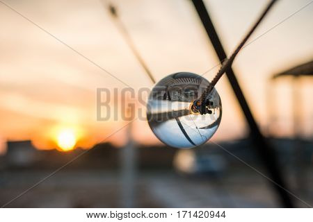 Street reflected inside the crystal ball. Sunset in Bulgaria