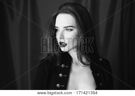 Black and white art photography monochrome beautiful girl with parted lips in black lingerie on red background looking away. Fashion photography. Bright appearance. Woman posing hands