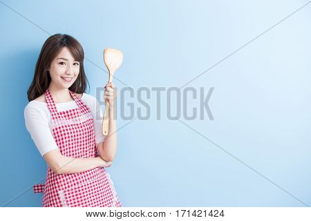 beauty housewife take rice spoon and smile isolated on blue background