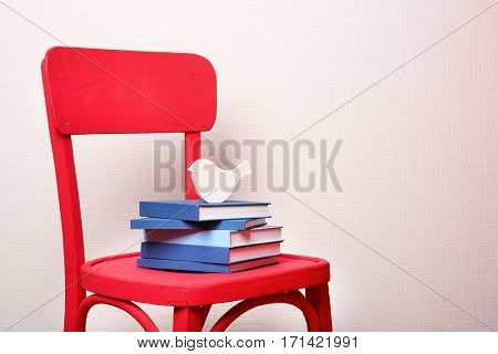 Stack of books on red chair against white wall background