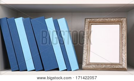 Set of books in row with frame, on white wooden shelving