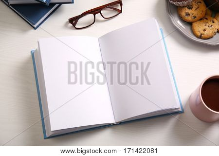 Open book on white wooden table