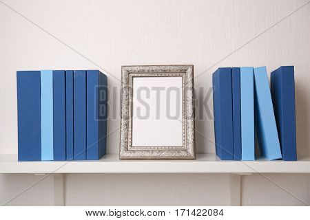 Set of books in row with frame, on white wooden shelf